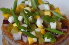 les petits dés de cornichons, d'oignons rouges et d'œuf dur avec un filet d'huile d'olive