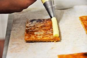 Avec une poche à dresser  répartir une couche régulière de crème mousseline en laissant un espace au centre pour ajouter les fraises.
