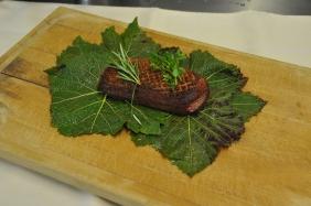 Sur le plan de travail, disposer à l'envers trois feuilles de vigne en les chevauchant légèrement et y déposer un magret